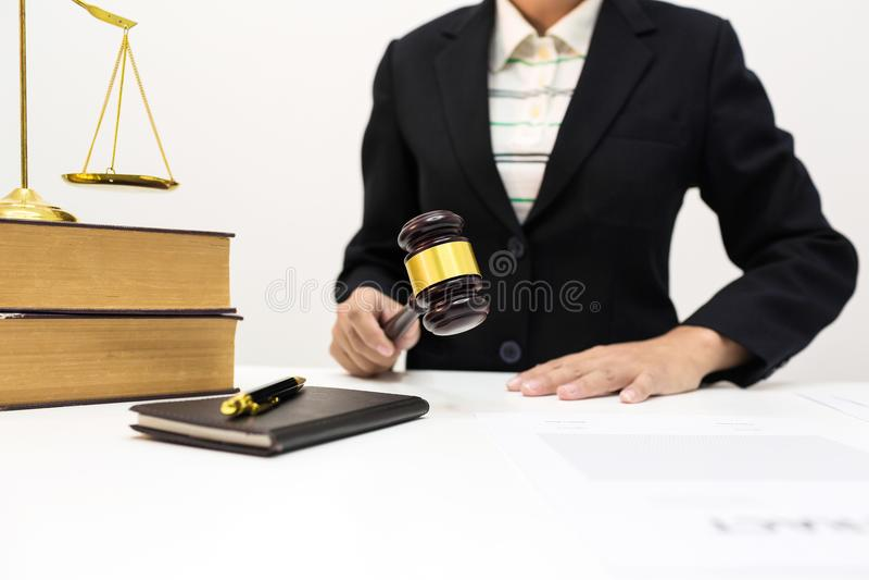 Advogado fêmea que guarda o martelo escuro de madeira na sala do escritório fotos de stock