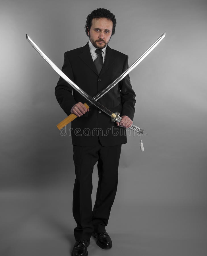 Advogado, homem de negócios agressivo com as espadas japonesas no defensivo fotografia de stock royalty free
