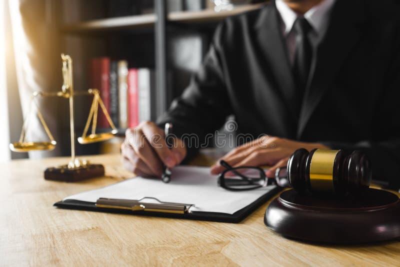 Advogado masculino no escritório com a escala de bronze na tabela de madeira fotografia de stock royalty free