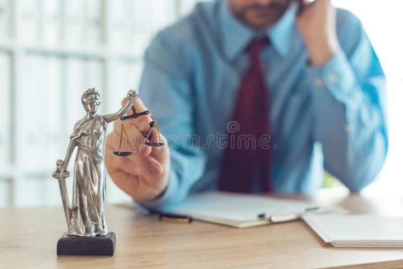 Advogado que fala no dispositivo móvel e que joga com escala de justiça fotos de stock