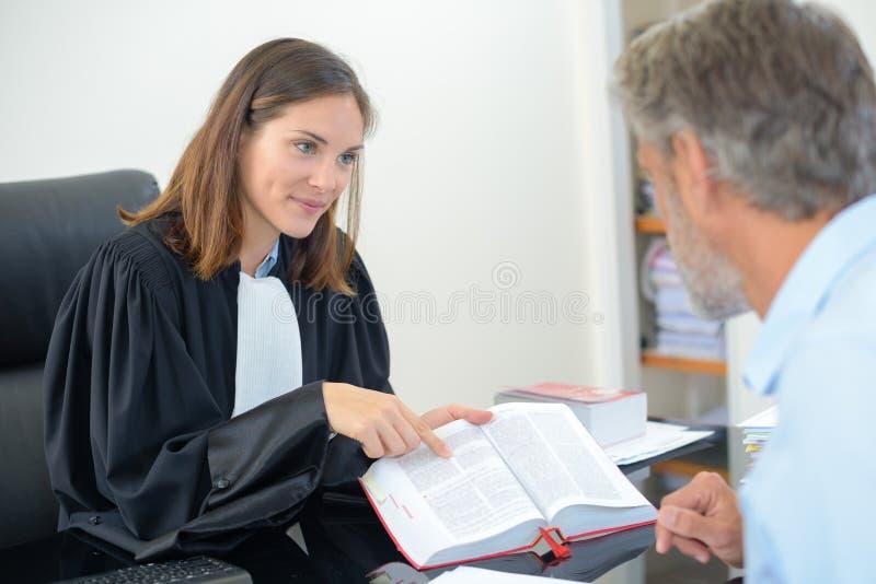 Advogado que mostra o texto do livro ao cliente foto de stock