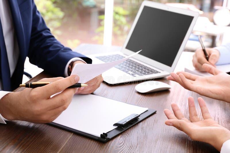 Advogado que trabalha com os clientes na tabela no escritório fotografia de stock royalty free