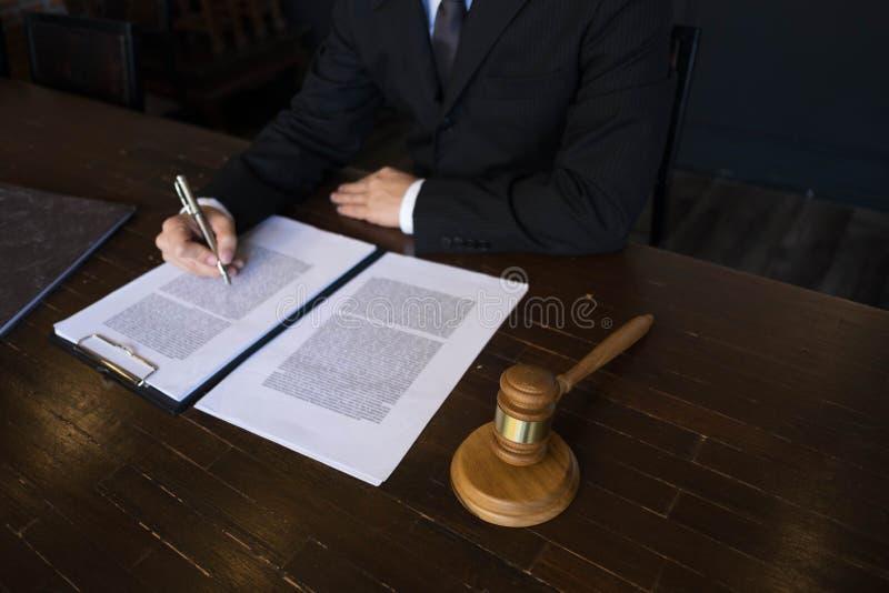 Advogado que trabalha com pap?is do contrato na tabela no escrit?rio advogado do consultante, advogado, juiz da corte, conceito fotografia de stock