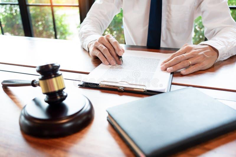 Advokat- eller domareaffärsman som arbetar med den skrivbordsarbeteöverenskommelseavtalet och auktionsklubban i rättssal-, rättvi arkivfoton