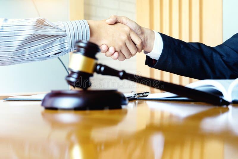 Advokat- eller domareauktionsklubba med j?mviktshandskakningen med klienten royaltyfria foton