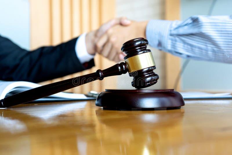 Advokat- eller domareauktionsklubba med j?mviktshandskakningen med klienten royaltyfri bild