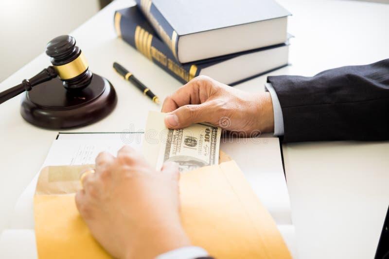 Advokat som erbjuds motta pengar som muta från klient på skrivbordet i rättssal royaltyfri foto