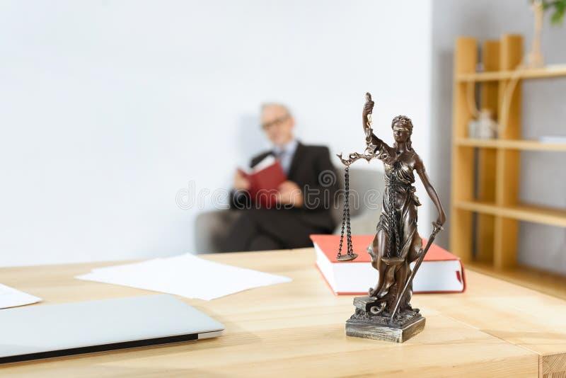 Advokatarbetsplats med themisstatyn arkivbilder