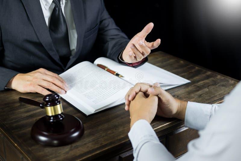 Advokaten eller domaren konsulterar möte med klienten på en advokatbyrå om laglig lagstiftning i rättssal med domareauktionsklubb royaltyfri bild