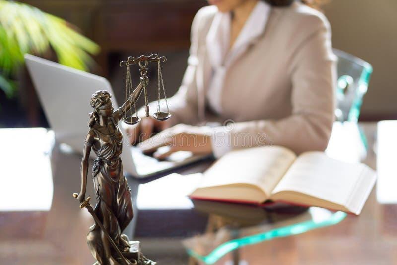 Advokatkontor Staty av rättvisa med våg och advokaten som arbetar på en bärbar dator arkivbild