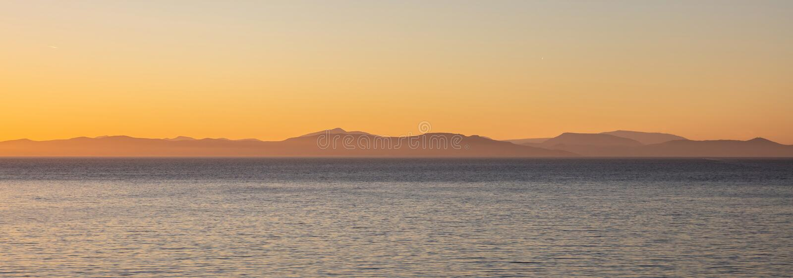 Aegean sea and Attica Greece hills, view from Kea island at sunset time, clear sky background, banner. Aegean sea and Attica Greece hills, view from Kea island royalty free stock images