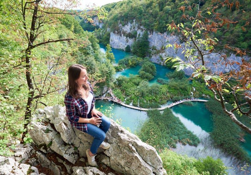 Aeirial视图年轻愉快的妇女坐石头,享受五颜六色的春天全景美丽的景色  图库摄影