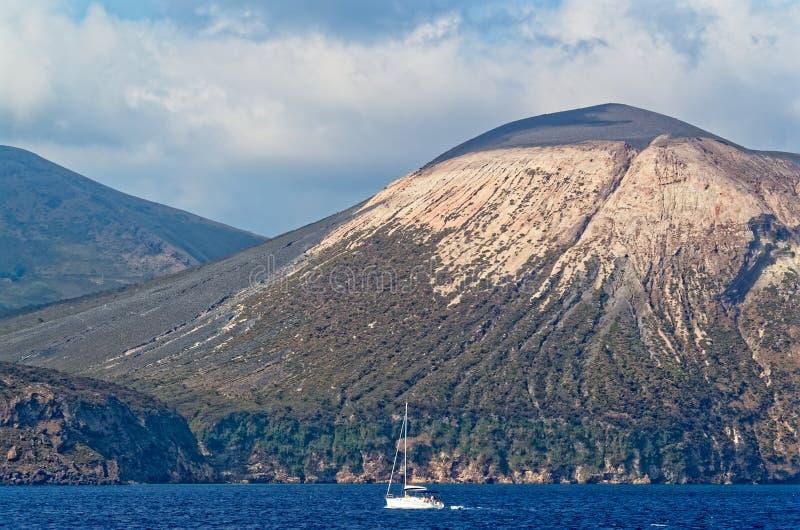 Aeolian Islands, Lipari island, Italy. Aeolian Islands in Italy, Lipari island with a sailing boat if foreground from a touristic ship royalty free stock photography