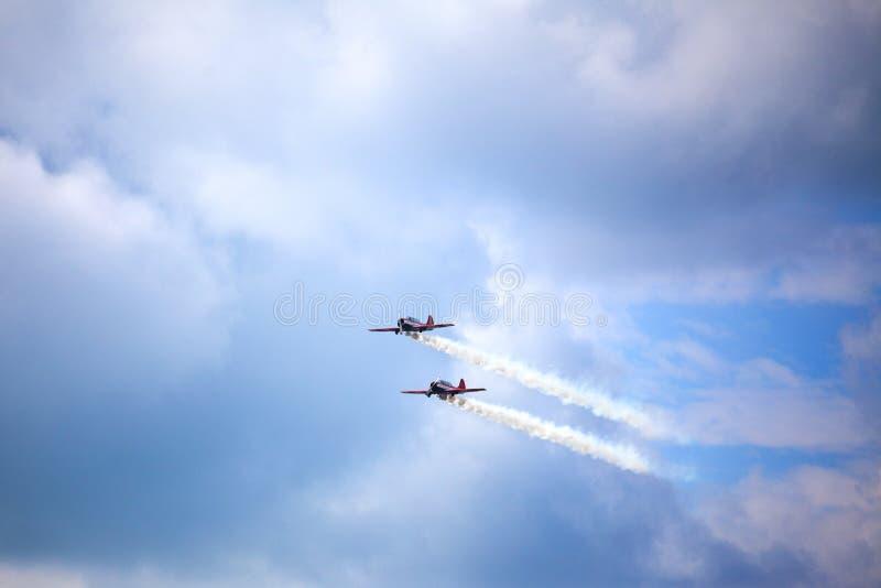 Aeródromo de Mochishche, festival aéreo local, dois Yak-52, equipe aerobatic 'céu aberto ', Barnaul, no céu azul com fundo das nu foto de stock