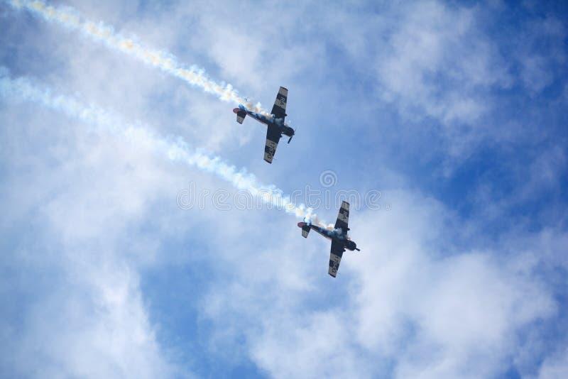 Aeródromo de Mochishche, festival aéreo local, dois Yak-52, equipe aerobatic 'céu aberto ', Barnaul, no céu azul com fundo das nu imagens de stock