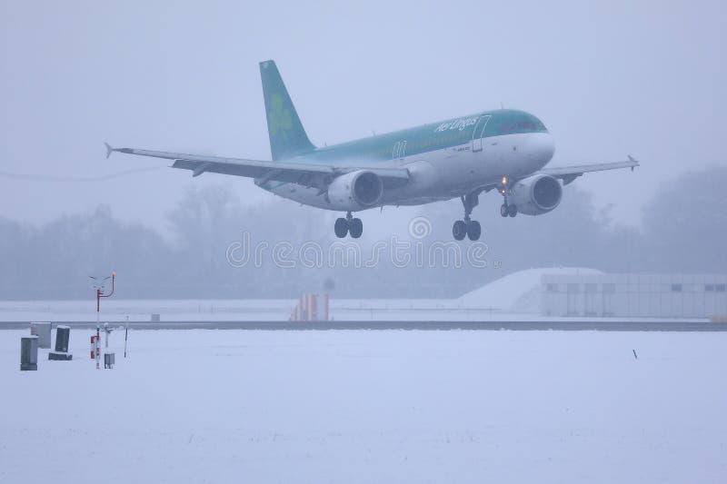 Aer Lingus nivå som tar av från den Munich flygplatsen MUC, snö arkivfoto