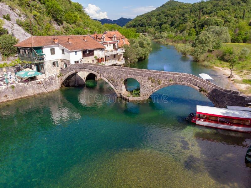 Aeralsikt till den gamla bron i byn Rijeka Crnojevica som reflekterar i vattnet i Montenegro mest stari royaltyfria bilder