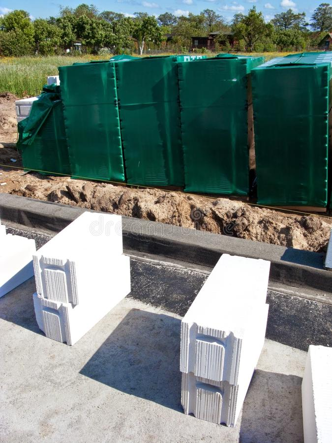 Aerated concrete blocks. Home building materials - aerated blocks or bricks ready to be used for walls construction. Piles of them wrapped in green plastic cover stock images