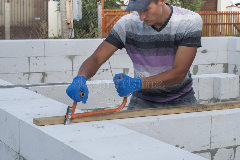 Aerated concrete masonry. Builder makes a groove in aerated concrete royalty free stock photo