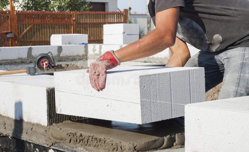 Aerated concrete masonry. Builder puts on grout aerated concrete block royalty free stock photos