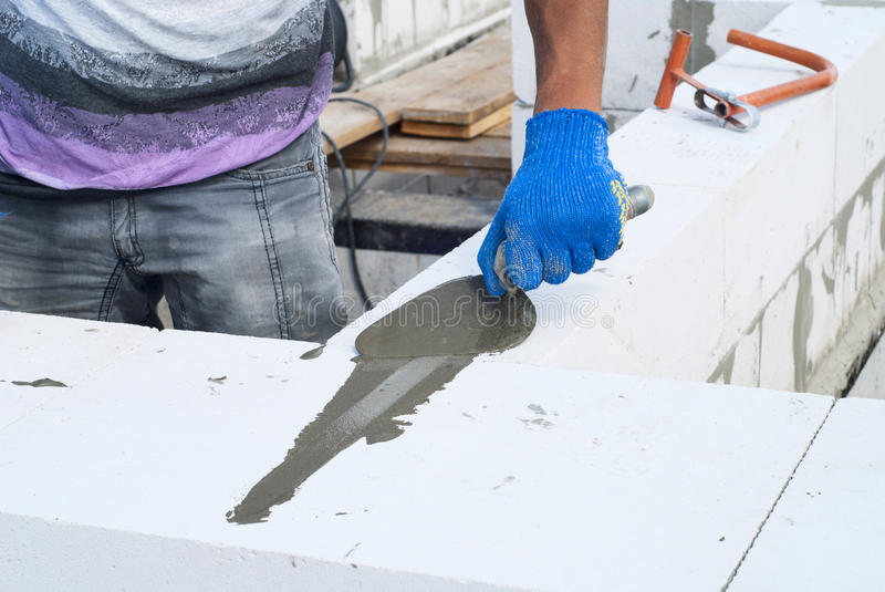 Aerated concrete masonry. Builder reinforces laying of aerated concrete blocks stock photos