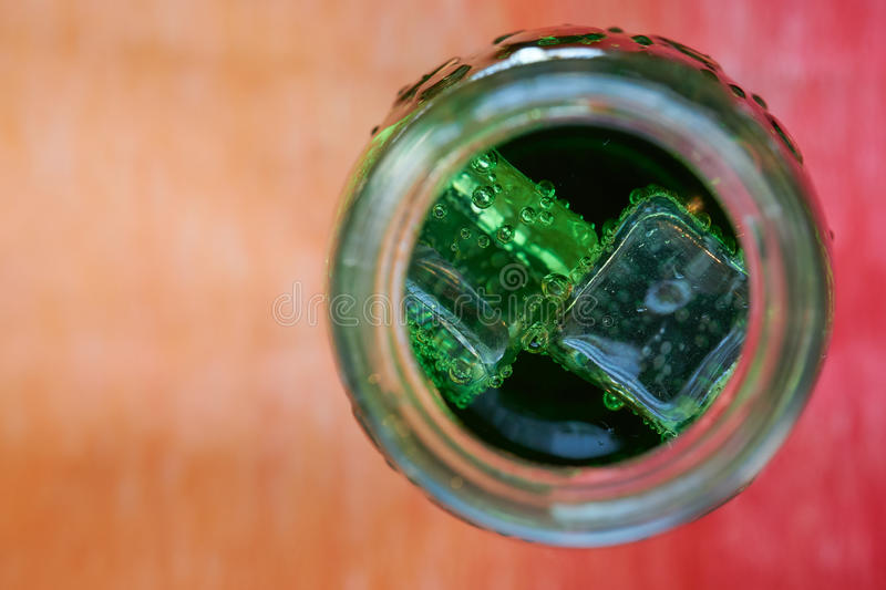 Aerated water bottle from the top. With ice cubes in green color stock photos