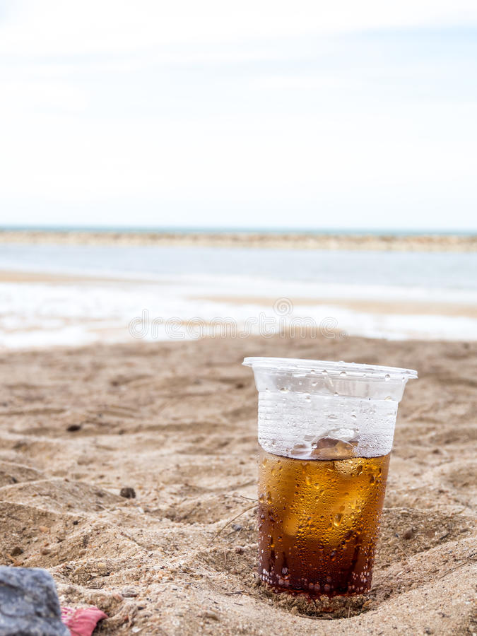 Aerated water. Hot summer glass plastic sparkling water in sand royalty free stock photo