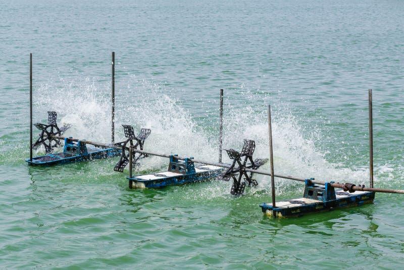 Aerator. Turbine wheel fill oxygen into water in lake stock image