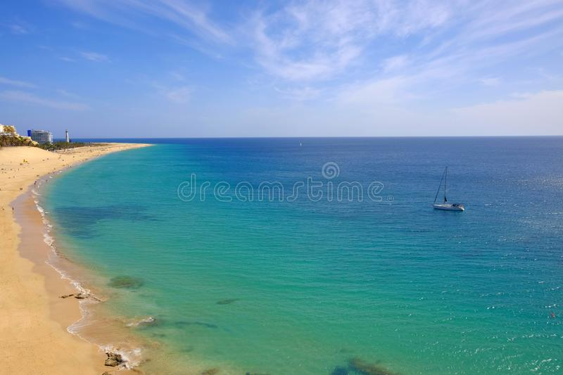 Aereal view on the Beach in Morro Jable, Fuerteventura, Canary Islands. View on the beach with golden sand and a sailboat in the ocean close to the coast stock photo