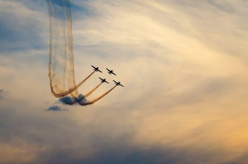 Aerei acrobatici fumosi sul cielo variopinto fotografia stock