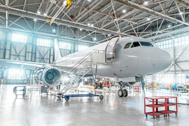 Aerei nell'ambito di manutenzione, controllante i sistemi meccanici per vedere se ci sono operazioni di volo Aereo nel capannone fotografia stock libera da diritti