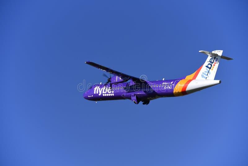 Aereo dell'aereo di linea di ATR 72 di Flybe che decolla in cielo blu fotografie stock libere da diritti