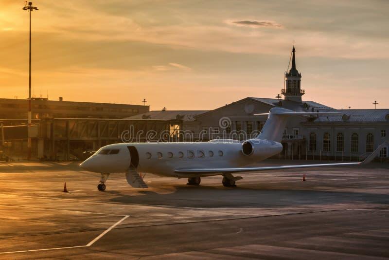 Aereo di affari con la porta aperta da una scala alla luce uguagliante dorata sul grembiule dell'aeroporto vicino al terminale fotografia stock