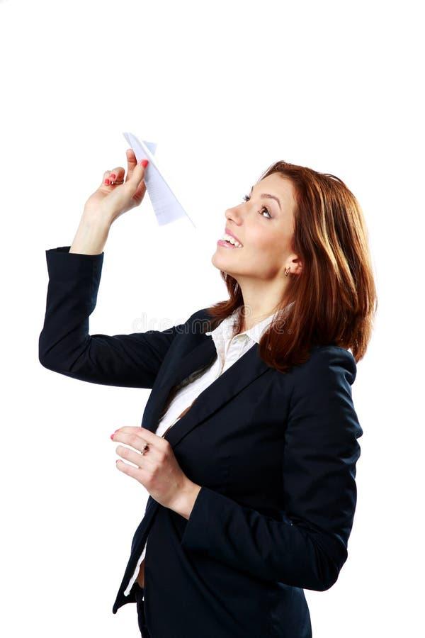 Aereo di carta di lancio della donna di affari felice immagine stock