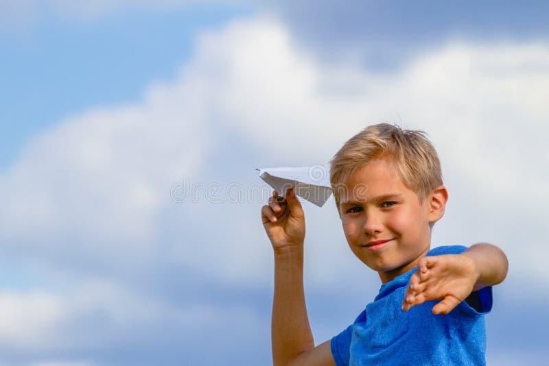 Aereo di carta di lancio del ragazzo il giorno di estate immagini stock libere da diritti