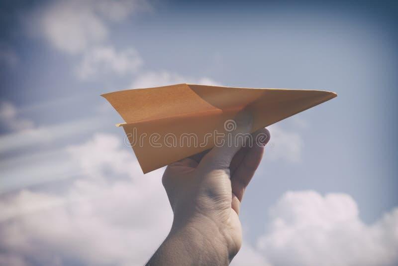 Aereo di carta in una mano contro il cielo nuvoloso immagine stock