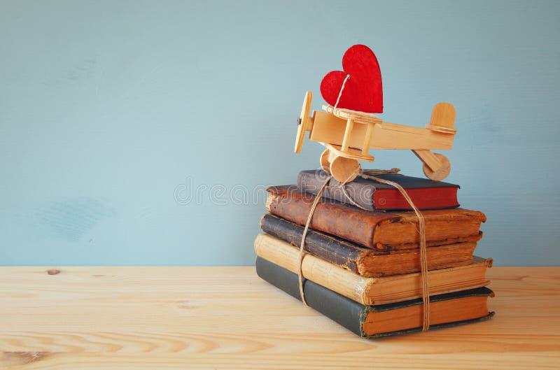 Aereo di legno con cuore sulla pila di vecchi libri fotografia stock