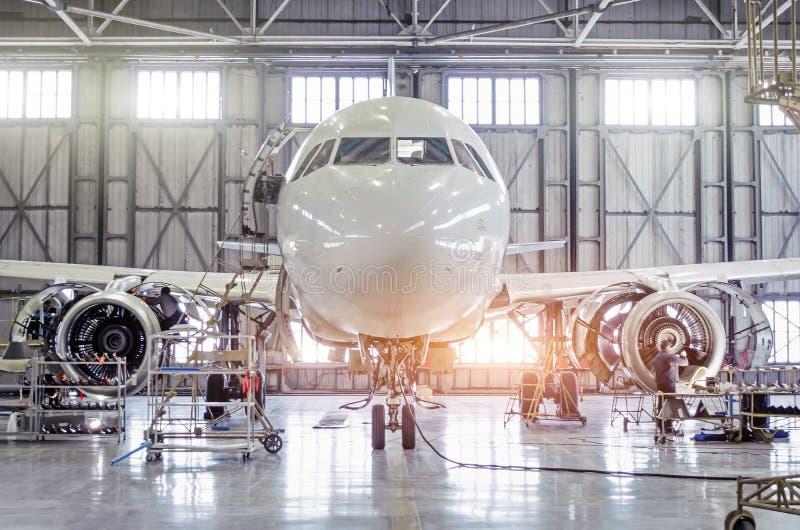 Aereo di linea su mantenimento della riparazione della fusoliera e del motore nel capannone dell'aeroporto immagini stock