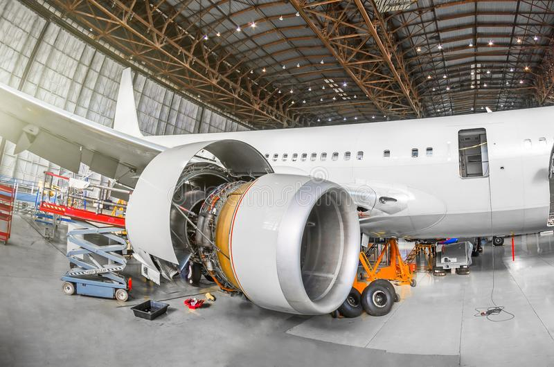 Aereo di linea su mantenimento della riparazione della fusoliera e del motore nel capannone dell'aeroporto Motore dell'aeroplano  immagini stock
