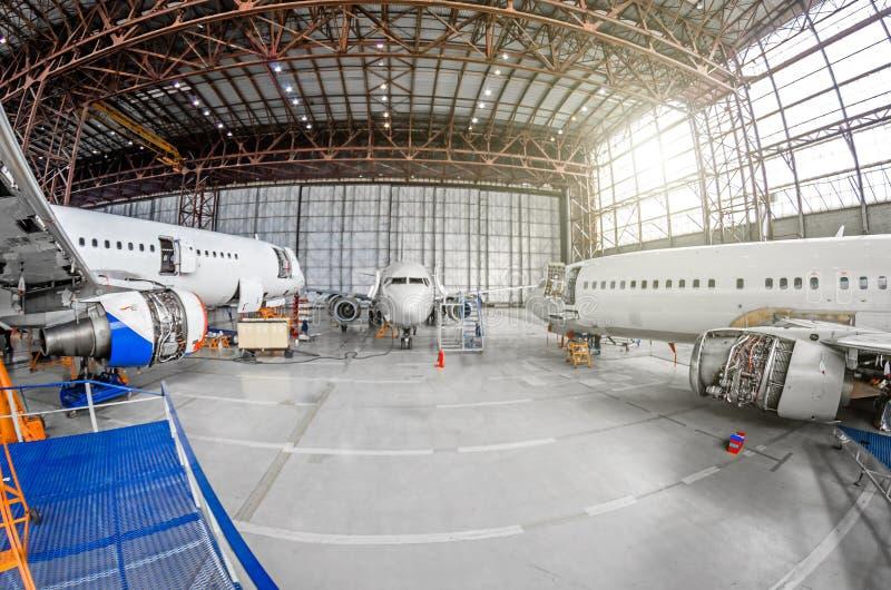 Aereo di linea tre su mantenimento della riparazione della fusoliera e del motore nel capannone dell'aeroporto immagine stock libera da diritti