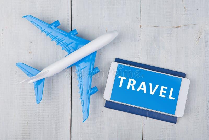 aereo, passaporto e smartphone con la parola & x22; TRAVEL& x22; sulla tavola di legno bianca immagine stock
