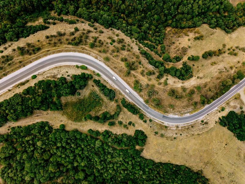 Aerial above view of a rural landscape with a curvy road running through it in Greece. royalty free stock photography