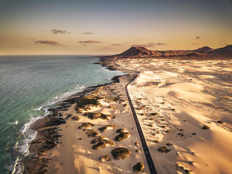 Aerial above view of yellow tropical sandy beach with black long way road and car traveling - ocean blue waves and shore - sunset. Time with long beautiful stock photo
