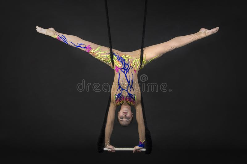 Aerial acrobat in the trapeze. A young girl performs the acrobatic elements in the air trapeze. Studio shooting performances on a black background stock image