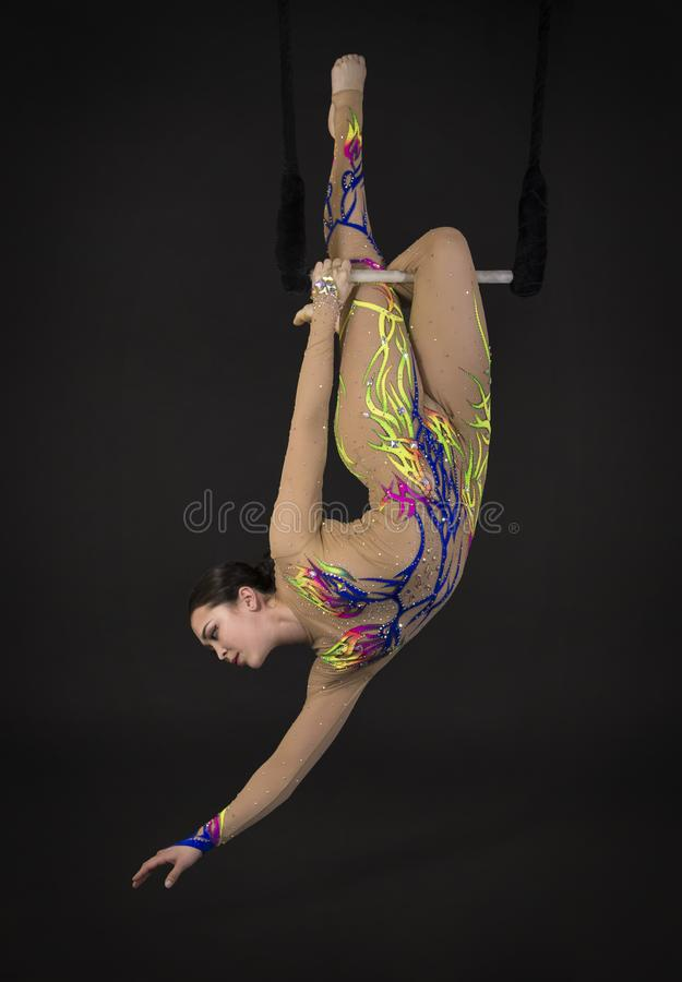 Aerial acrobat in the trapeze. A young girl performs the acrobatic elements in the air trapeze. Studio shooting performances on a black background royalty free stock images