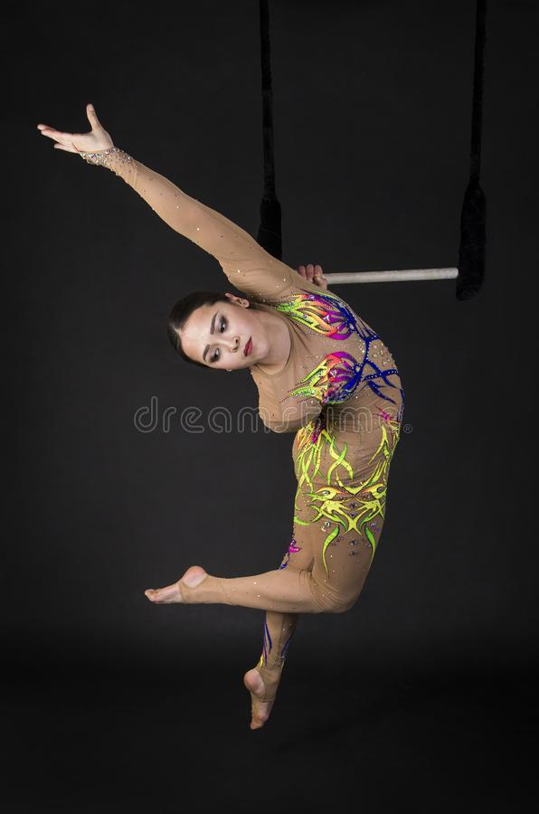 Aerial acrobat in the trapeze. A young girl performs the acrobatic elements in the air trapeze. Studio shooting performances on a black background stock photography