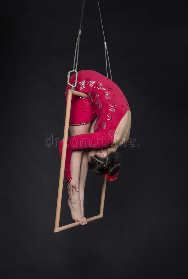Aerial acrobat in the trapeze. A young girl performs the acrobatic elements in the air trapeze. Studio shooting performances on a black background royalty free stock photo