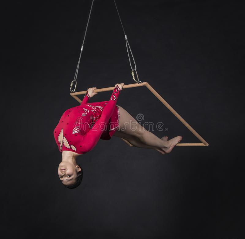 Aerial acrobat in the trapeze. A young girl performs the acrobatic elements in the air trapeze. Studio shooting performances on a black background stock photos