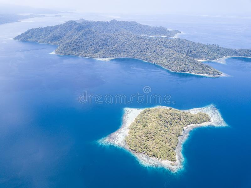 Aerial of Beautiful Islands and Coral Reefs in Raja Ampat. The beautiful islands found throughout Raja Ampat, Indonesia, are surrounded by healthy coral reefs stock photo