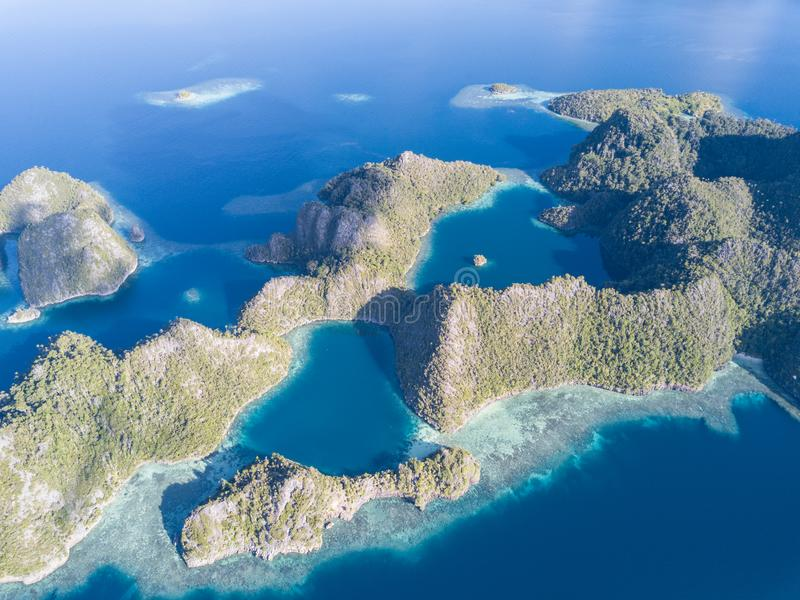 Aerial of Beautiful Limestone Islands in Raja Ampat. The limestone islands of Raja Ampat are surrounded by healthy, shallow coral reefs. This remote region in stock photo